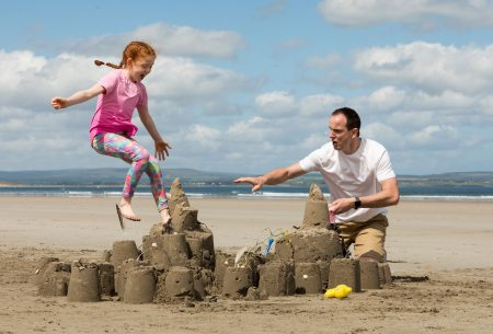 father and daughter building sandcastles at the beach